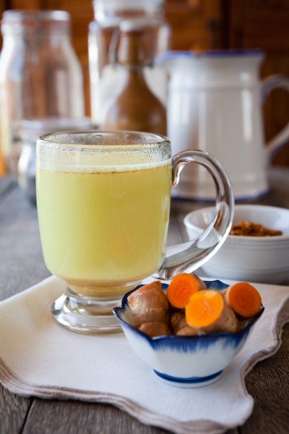 Golden milk. Turmeric herbal medicine, an anti-inflammatory. Shallow DOF, focus on the brim of the glass and the foam on milk