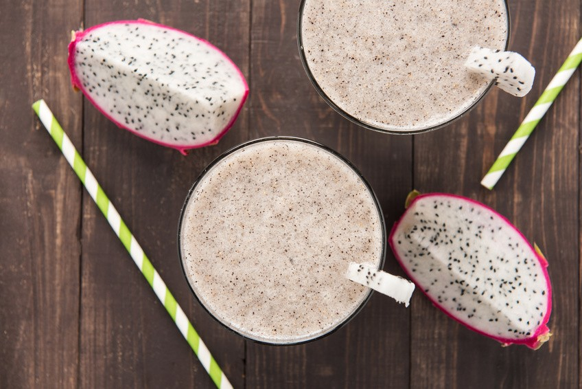 Dragon fruit smoothie and drinking straw on wooden background