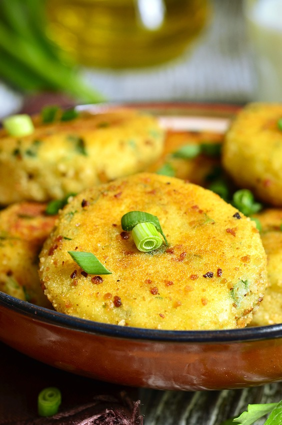 Homemade potato patties with herbs and green onion on rustic background.